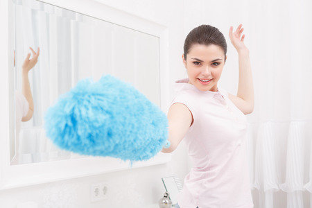 epee: Hold on. Excited woman acting like fences with epee, holding cleaning sweep instead of epee