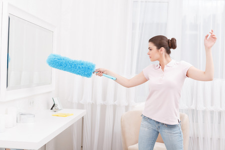 epee: I will win. Young woman acting like fences with epee, holding cleaning sweep instead of epee