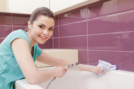 cleaning lady: Joyful work. Youthful lady cleaning bathroom with help of white cloth