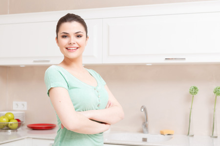 lady: Serious attitude. Young smiling lady standing in kitchen with her arms folded across her chest
