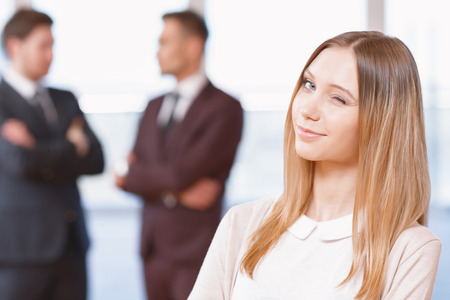 coworkers: Office workers. Blond young business woman standing in foreground giving a wink, her co-workers discussing business matters