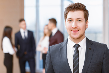 coworkers: Office workers.  Young business man standing in foreground smiling, his co-workers discussing business matters  Stock Photo