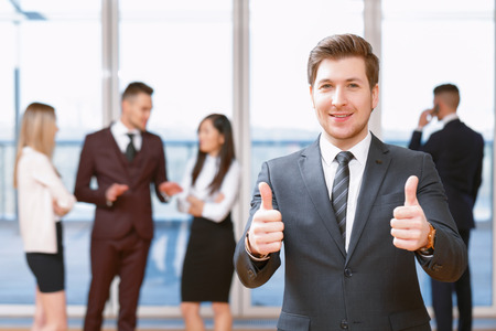 coworkers: Business success.  Young business man standing in foreground smiling and showing thumbs up , his co-workers discussing business matters Stock Photo