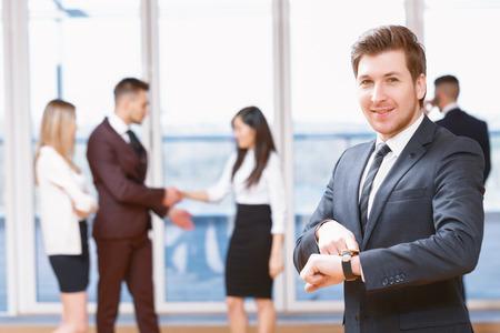 llegar tarde: No llegues tarde para la reunión. Hombre de negocios joven que se coloca en primer plano sonriendo y apuntando a su reloj, sus compañeros de trabajo discutiendo asuntos de negocios en el fondo