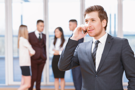 coworkers: Phone call.  Young business man standing in foreground smiling and talking on the phone, his co-workers discussing business matters