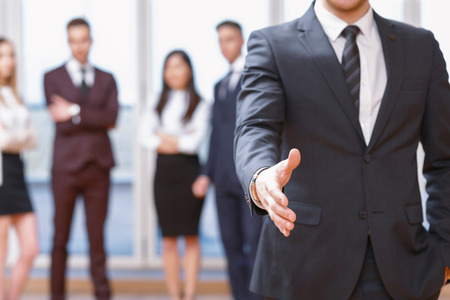 nice background: Nice to meet you.  Young business man standing in foreground extending hand for a handshake, his co-workers discussing business matters in the background