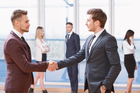 buen trato: Buen negocio. Dos jóvenes empresarios de pie en primer plano dando la mano mirando el uno al otro