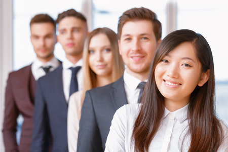 coworkers: Team in the office. Asian businesswoman standing in the foreground smiling, her team of co-workers Stock Photo
