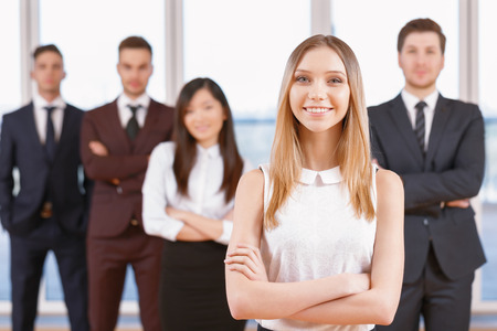 coworkers: Team in the office. Young blond businesswoman standing in the foreground smiling and holding her arms crossed, her team of co-workers in the background