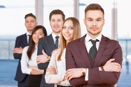 coworkers: Team in the office. Young handsome businessman standing in the foreground holding his arms crossed, his team of co-workers in the background Stock Photo