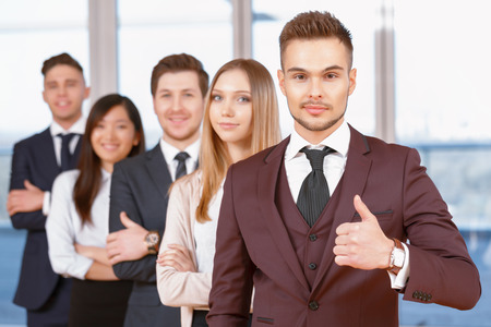 coworkers: Team in the office. Young handsome businessman standing in the foreground showing thumb up, his team of co-workers in the background