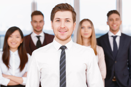 coworkers: Team in the office. Young handsome businessman standing in the foreground smiling, his team of co-workers