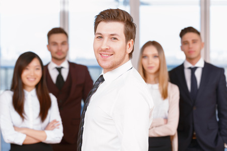 coworkers: Team in the office. Young handsome businessman standing in the foreground smiling side view , his team of co-workers in the background