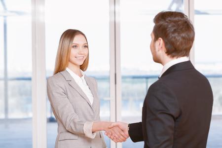 buen trato: Buen negocio. Empresaria joven y hombre de negocios dándose la mano en la oficina Foto de archivo