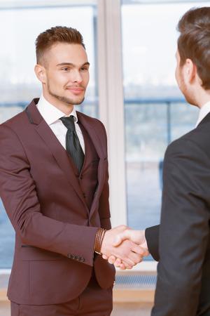 buen trato: Buen negocio. Dos hombres de negocios satisfechos j�venes agitando las manos en la sonrisa de la oficina