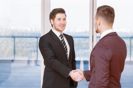 buen trato: Buen negocio. Dos hombres de negocios satisfechos jóvenes agitando las manos en la sonrisa de la oficina