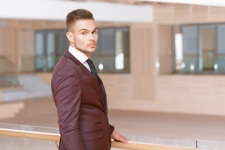 formalwear: Formalwear. Young handsome businessman standing in the office and looking at you