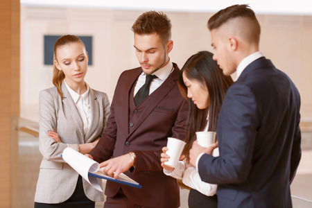 coworkers: New business plan. Co-workers discussing new business plan and drinking coffee during the coffee break at the meeting Stock Photo