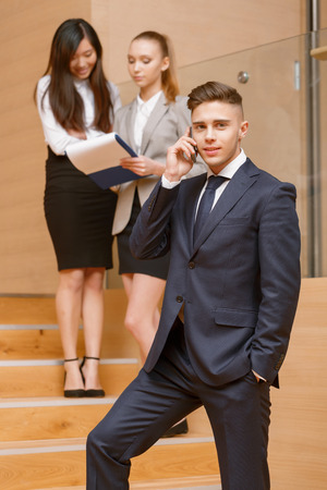 coworkers: Young businessman standing in the office and talking on the phone, his co-workers discussing business matters  Stock Photo