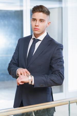 llegar tarde: No llegues tarde. Apuesto hombre de negocios joven que se coloca en la oficina y se�alando su reloj Foto de archivo