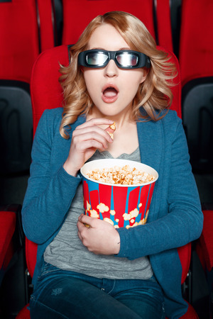 3 d: What story line. Amazed blond woman in 3 d glasses eating popcorn in cinema while watching film Stock Photo
