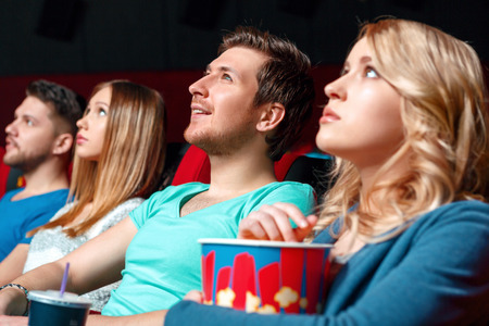 Breath-taking. Pretty blond woman with popcorn in cinema near other viewer.