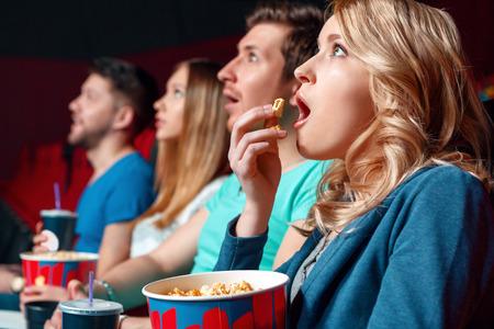 zábava: Emocionální film. Nadšený blond žena jíst popcorn v kině nejemotivněji v blízkosti jiných diváka.