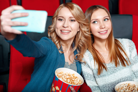 coke: Cinema selfie. Two beautiful smiling girls excited doing selsie in cinema with popcorn and coke. Stock Photo