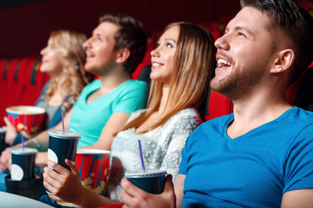 hilarious: Hilarious film. Young cinema visitor hoot with laugh holding cola and popcorn.
