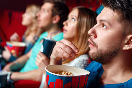 viewers: Waxy person. Really impressed cinema viewers with popcorn and cola, close up of young sensitive man eating popcorn.