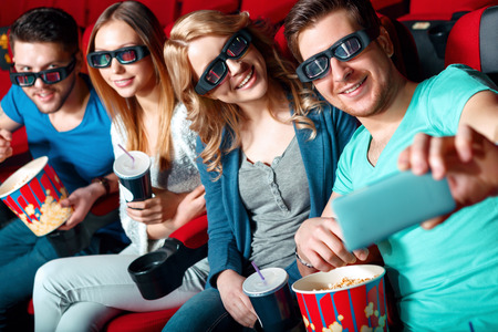 3 d: 3 d selfie. Group of cinema visitors in 3 d glasses doing selfie with popcorn and cola .