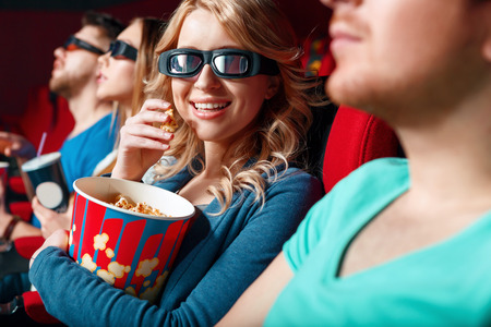 d: 3 d world. Pretty young smiling blond woman in 3 d glasses eating popcorn slightly hugging its box. Stock Photo
