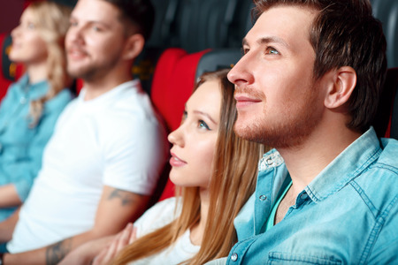 charmed: Love story. Couple of young charmed watching film people in cinema.