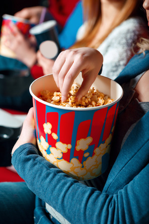cinema people: So tasty. Close up of woman taking popcorn out of box in cinema.