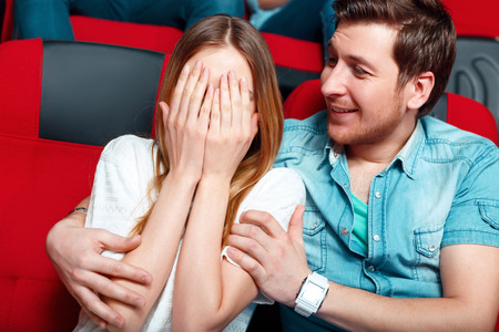 I am afraid. Young woman shielding her eyes with her hand in cinema and her  male friend trying to calm her down.