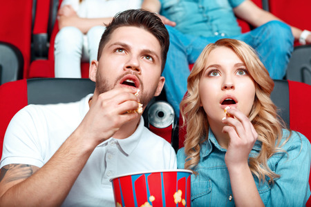 they are watching: Fully committed. Two young people fully interested in watching film so they opened their mouths and they eating popcorn.