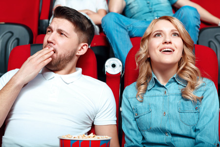 neighbor: We are different. Young beautiful blond woman very interested in watching film and her neighbor really feels bored.