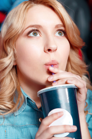 Rapturous girl. Young blond woman enthusiastically watching film and drinking coke in cinema Stock Photo