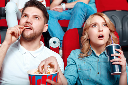 they are watching: So exciting. Two young people really interested in watching film so they opened their mouths and they eating popcorn and drinking cola  Stock Photo