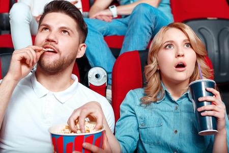 palomitas de maiz: Tan emocionante. Dos jóvenes muy interesados ??en ver la película por lo que abrieron la boca y comer palomitas y bebiendo refrescos de cola