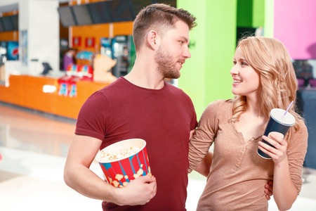 Soft glance. Pair of young people standing and looking at each other and holding popcorn and coke. photo