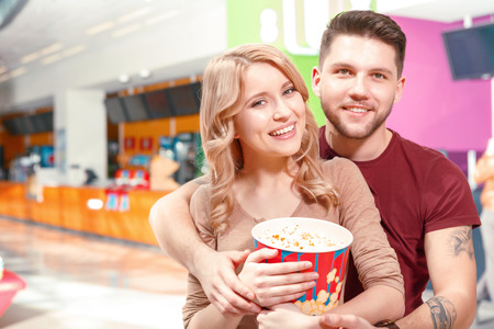 Lets hug. Couple of young smiling people standing and hugging in hall with popcorn before watching film in cinema photo