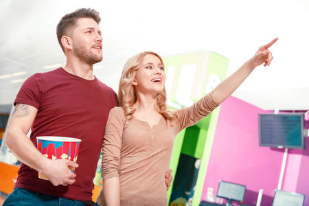 Look there. Couple of young smiling people standing in hall pointing upwards and holding popcorn before watching film in cinema. photo