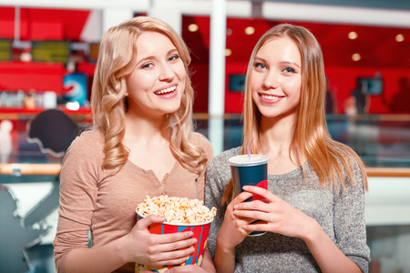 Earnest glance. Two pretty women with cola and popcorn in hall before watching film in cinema. photo