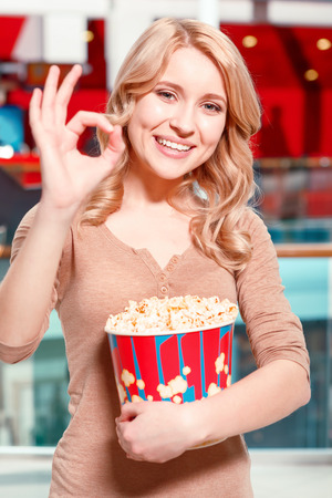 Everything is OK. Young blond woman standing in hall before watching film in cinema with popcorn showing OK. photo