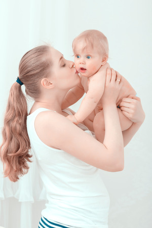 surprised baby: Parenthood. Young mother holding and kissing her surprised baby