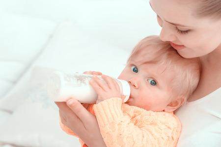 La alimentación de un bebé. Viendo Madre y abrazando a su bebé que come de la botella