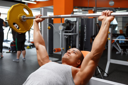 gym: Pushing up.  Lying handsome powerful man lifting barbell in sport gym.