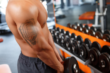 tatoos: Powerful muscles. Close up of muscular man with tatoos working out with dumbbell in gym. Stock Photo