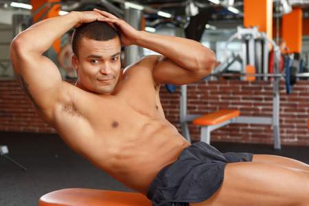 crunches: Charming glance. Young-looking muscular man doing abdominal crunches in sport gym.